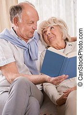 Reading book together - Senior happy couple reading book...