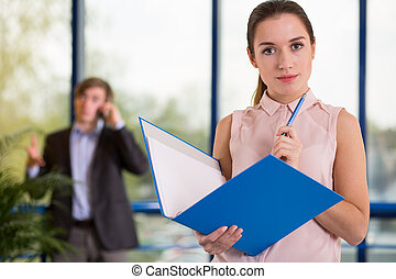 Office worker holding blue folder - Beauty female office...