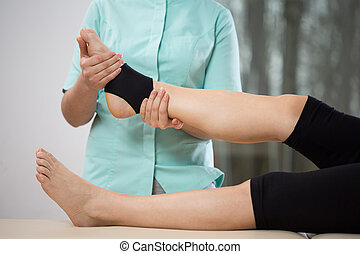 Ankle manipulation - Young physiotherapist doing ankle...