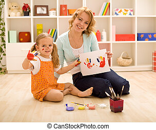 Girls having fun painting hands - Woman and little girl...