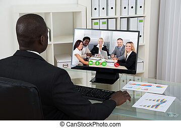 Businessman Video Chatting With Colleagues On Computer -...