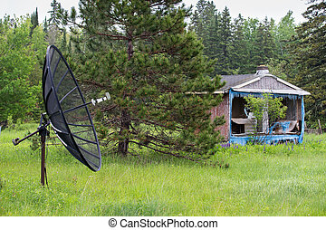 Satellite Dish in Front of an Abandoned House or Shack -...