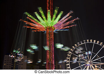 carousel and ferris wheel in an amusement park at night