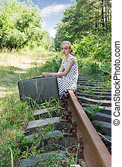Young traveling girl sitting on rail - Young girl in a...