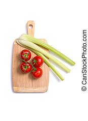 Fresh tomatoes and celery sticks on chopping board