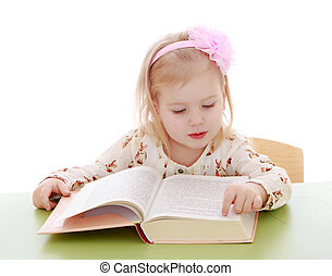 Little Caucasian blond girl sitting at a Desk and read by...