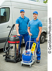 Two Cleaners Standing With Cleaning Equipments - Two Happy...