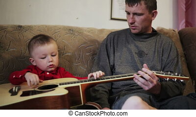 young father teaches his young son to play guitar