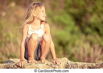 Happy Little girl  sitting on the beach