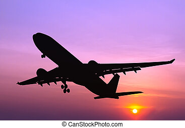 Silhouetted commercial airplane flying at sunset