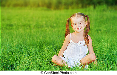 happy child little girl in  white dress lying on grass Summer