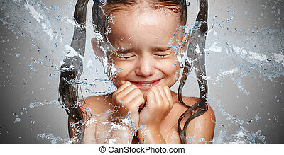 happy funny child girl in  spray of water laughs