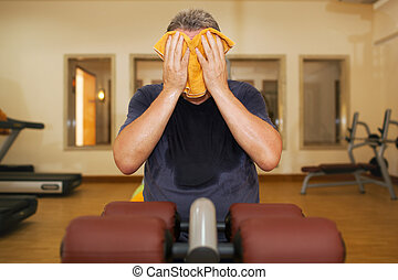 Man wiping face with a towel after training - Man in the...