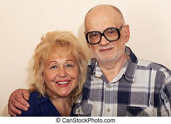 Smiling mature couple - Senior bearded man in glasses hugs...