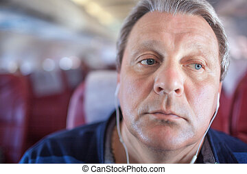 Man listening to music in the airplane - Close-up shot of...