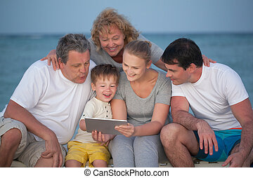 Happy big family with tablet PC on the beach - Child using...