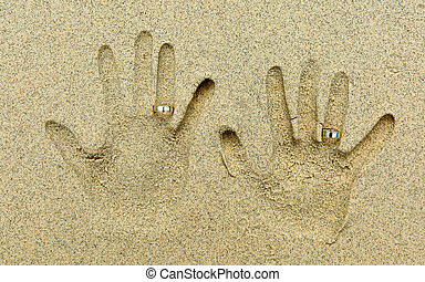 two wedding rings placed on fingers in the sand - Two Hand...