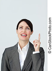 Positive businesswoman pointing at a copyspace