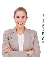 Radiant female executive with folded arms against a white...