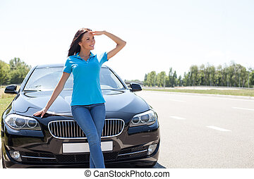 Cheerful young woman is relaxing on the road