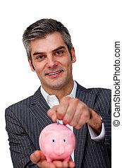 Self-assured Businessman saving money in a piggybank