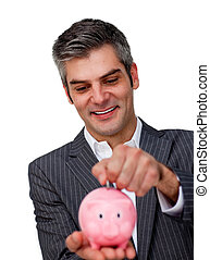 Assertive Businessman saving money in a piggybank