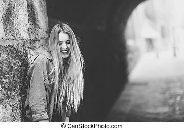 Happy blonde girl smiling in urban background - Portrait of...