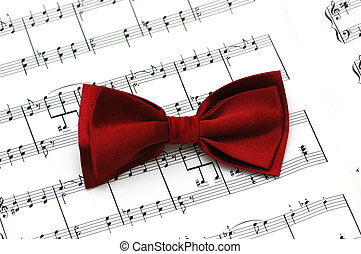 Red bow tie on musical notes paper - Red bow tie on musical...