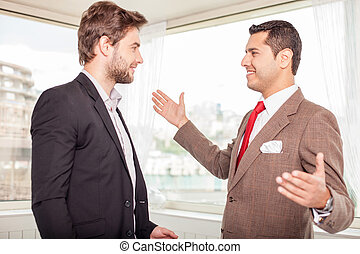Cheerful young colleagues are greeting each other - Two...