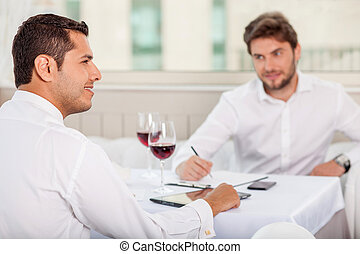 Successful young men has a business lunch in restaurant -...
