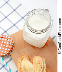 jug of milk on wooden plate with biscuit