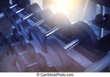Dumbbells in modern sports club. Weight training equipment....