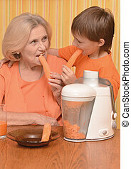 Woman and grandson eating carrots