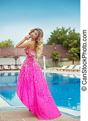 Beautiful girl model in pink fashion dress posing by blue...