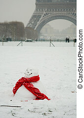 Rare snowy day in Paris. Funny snowman with red scarf and...
