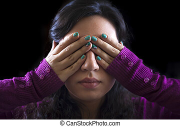 Woman covering her eyes with her hands on a black background...