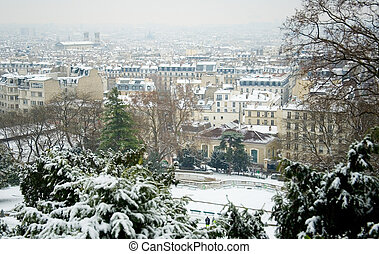 Rare snowy day in Paris. Parisian roofs covered with snow,...