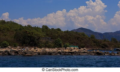 view of stony shore with white clouds in sky over green...