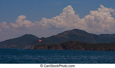 view of kite surfing against clouds sky and mountains -...
