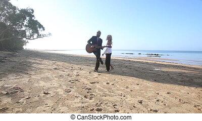 blonde guitarist plays on beach blonde girl flirts at dawn