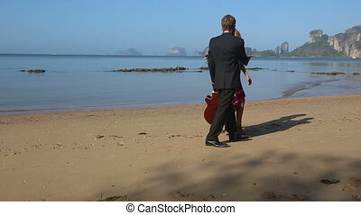 guitarist holds hand to girl in red swings and hugs on beach...