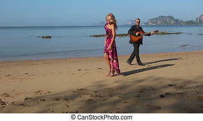 girl in red stands and guitarist walks around plays on beach