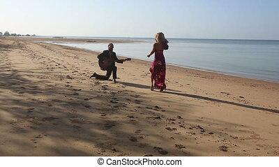 guitarist plays standing on knee girl in red dances on beach...