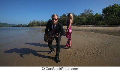 guitarist looks into camera waves hand under low tide - guy...