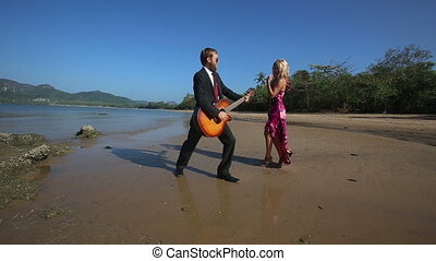 guitarist plays inspiredly and girl disturbs under low tide