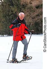 Senior Man Snowshoeing - Senior man snowshoeing. Vertically...