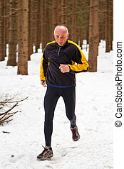 Senior Man Joggin in Snow - Senior man jogging in winter...