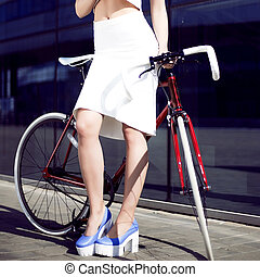 young beautiful blonde in city with bicycle drinks water