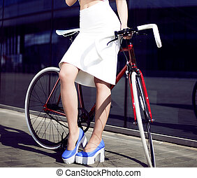 young beautiful blonde in city with bicycle drinks water -...