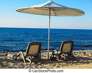 Two deckchairs and umbrella on blue sea sand beach - Two...